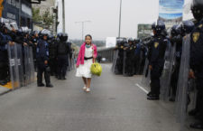 A girl walks past riot policemen guarding one of the access roads to Benito Juarez International airport after demonstrators staged a protest over the 43 missing Ayotzinapa students in Mexico City November 20, 2014. Forty-three missing students abducted by corrupt police in southwest Mexico weeks ago were apparently incinerated by drug gang henchmen and their remains tipped in a garbage dump and a river, the Mexican government said.  REUTERS/Tomas Bravo (MEXICO - Tags: SOCIETY CIVIL UNREST POLITICS TPX IMAGES OF THE DAY)